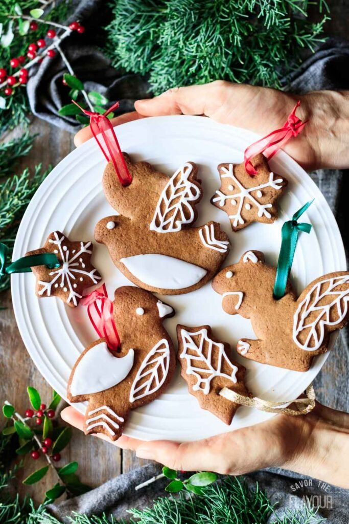 person holding a plate of gingerbread cookie ornaments
