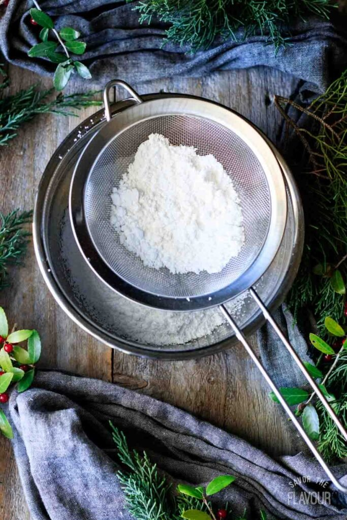 sifting icing sugar into a mixing bowl