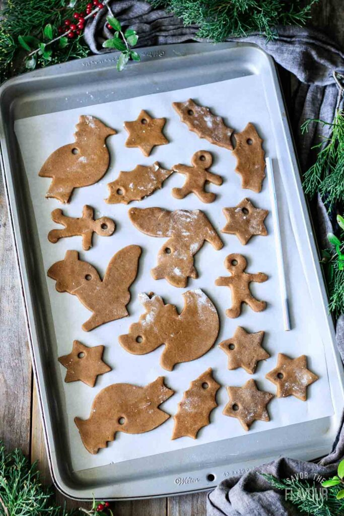 cutting holes in the gingerbread cookies with a straw