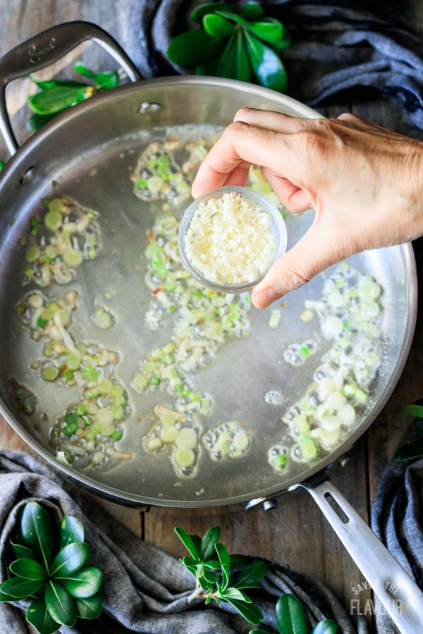 adding garlic to sauteed spring onions