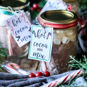 two jars of hot cocoa mix with candy canes and gift tags