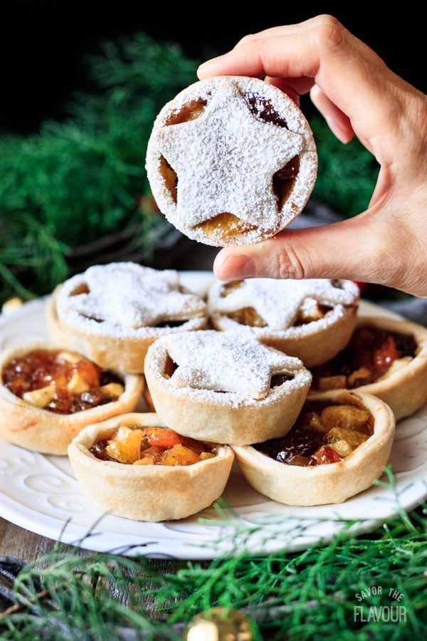 person holding a mincemeat tart with a star on top