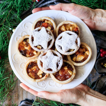 person holding a plate of mincemeat tarts