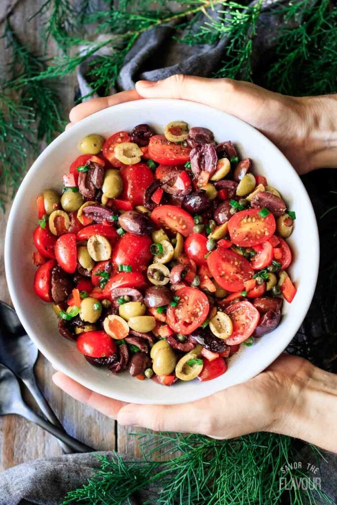 person holding a bowl of tomato olive salad