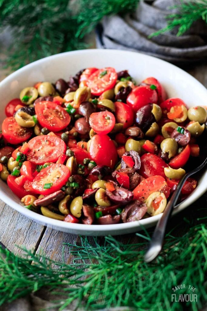 bowl of tomato olive salad with a spoon