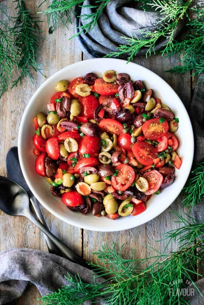 bowl of tomato olive salad with two spoons