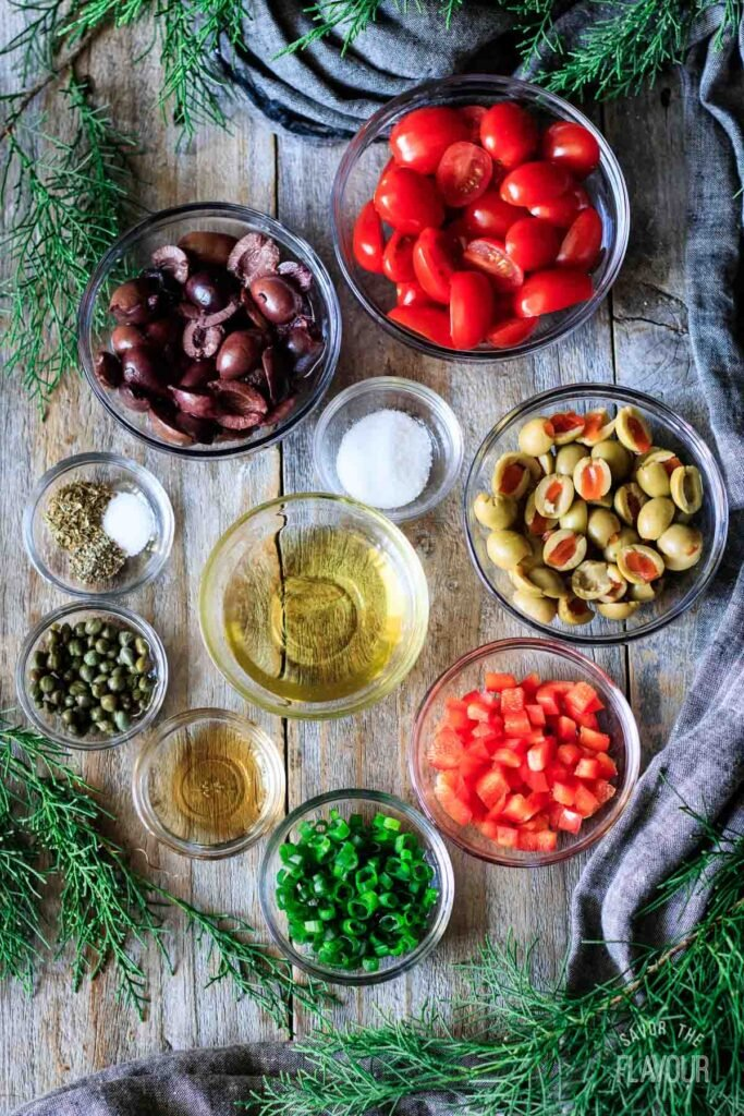 ingredients for tomato olive salad in glass bowls
