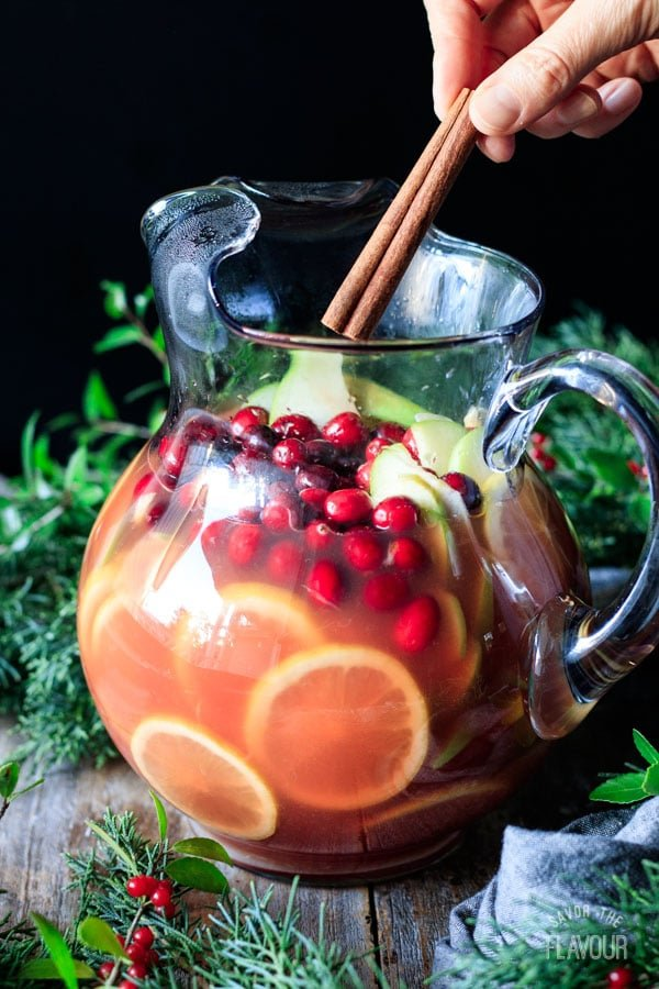 adding a cinnamon stick to a pitcher of winter sangria