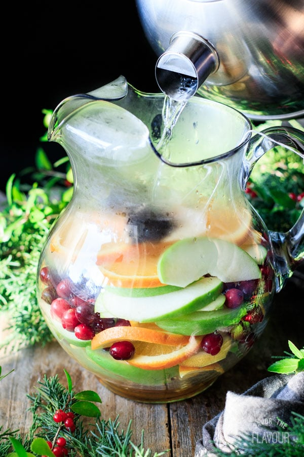 pouring boiling water into a glass pitcher of fruit
