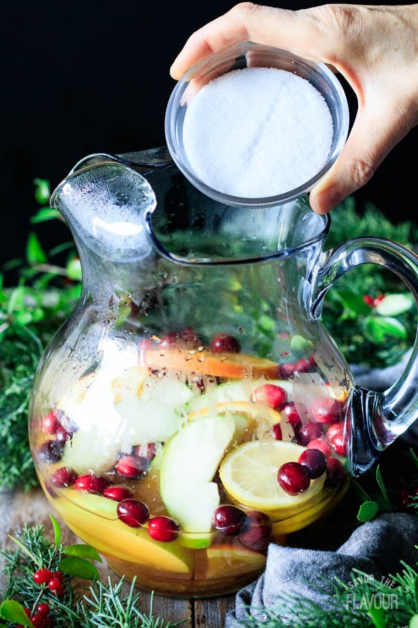 adding sugar to the fruit and tea mixture