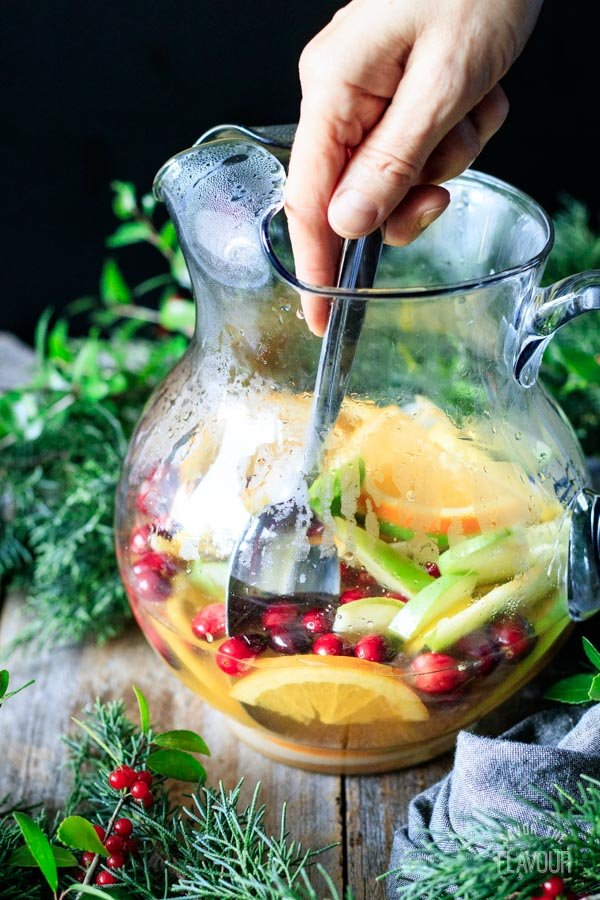 stirring the tea, fruit, and sugar in a glass pitcher