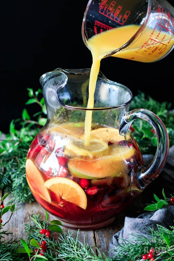 pouring orange juice into a pitcher of winter sangria