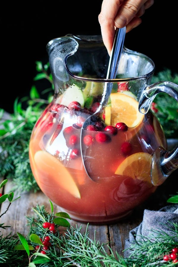 stirring a pitcher of winter sangria