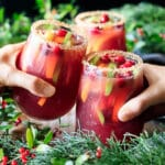 people doing a toast with two glasses of winter sangria