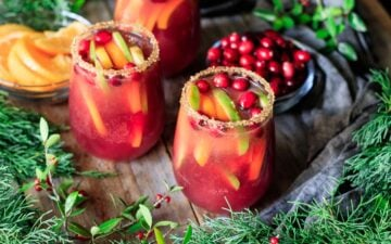two glasses of winter sangria with oranges and cranberries
