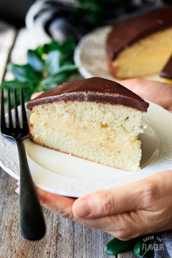 person holding a plate of Boston cream pie