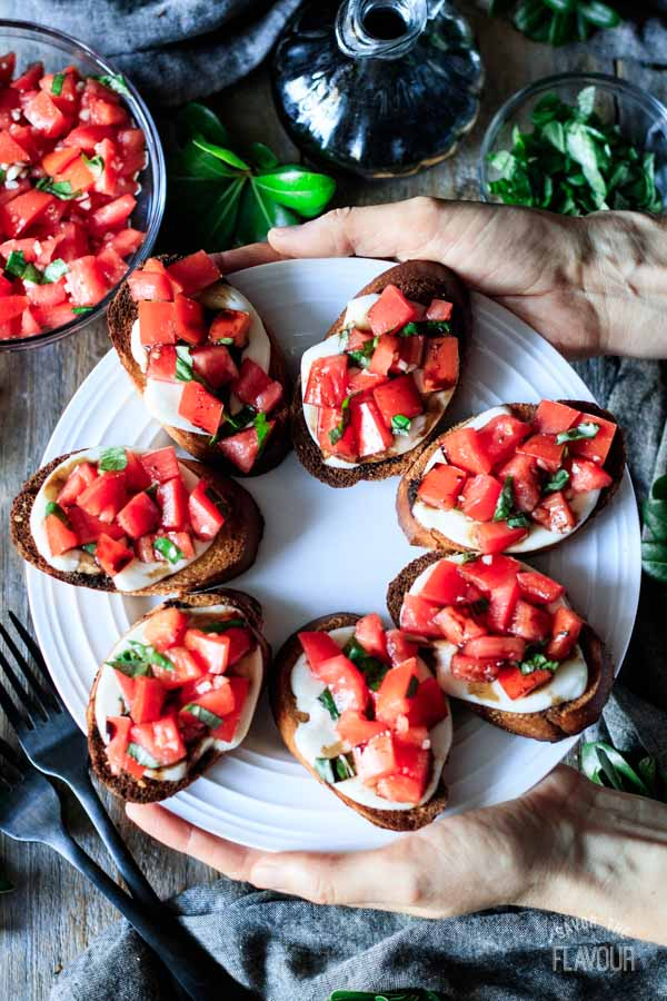 person holding a plate of Caprese bruschetta