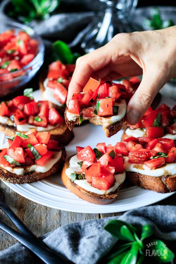person holding a piece of Caprese bruschetta