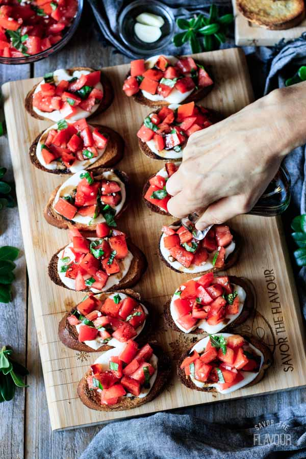 person pouring balsamic reduction on Caprese bruschetta