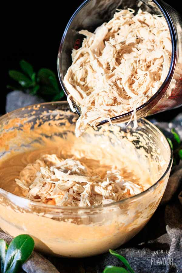 dumping shredded chicken into the cream cheese mixture