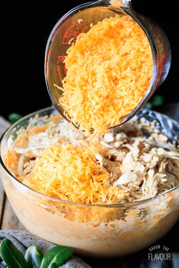 person dumping shredded cheddar into chicken dip
