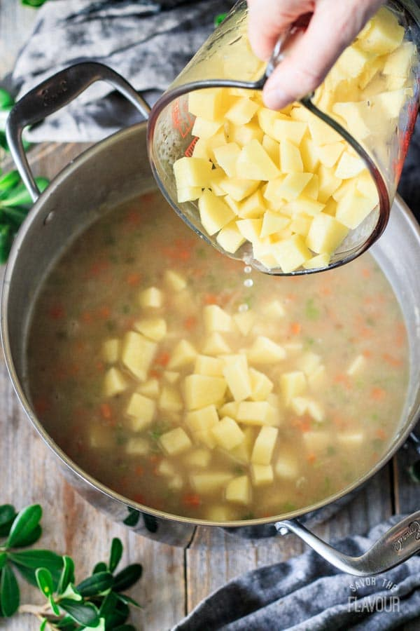 person dumping cubed potatoes into a pot of chowder