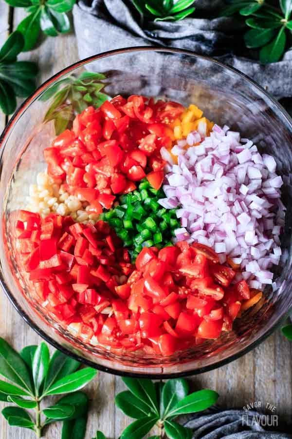 tomatoes, onion, peppers, beans, and corn in a bowl