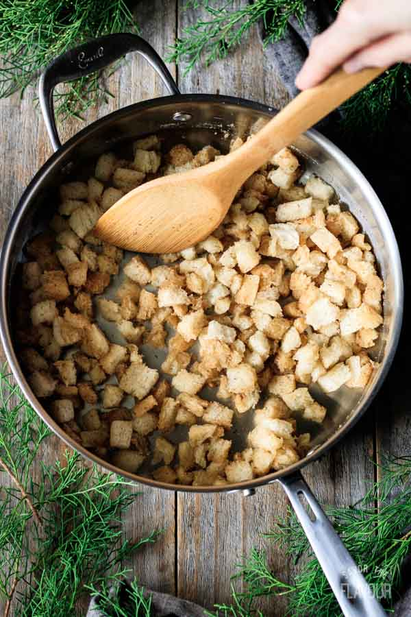stirring bread cubes with melted butter in a skillet