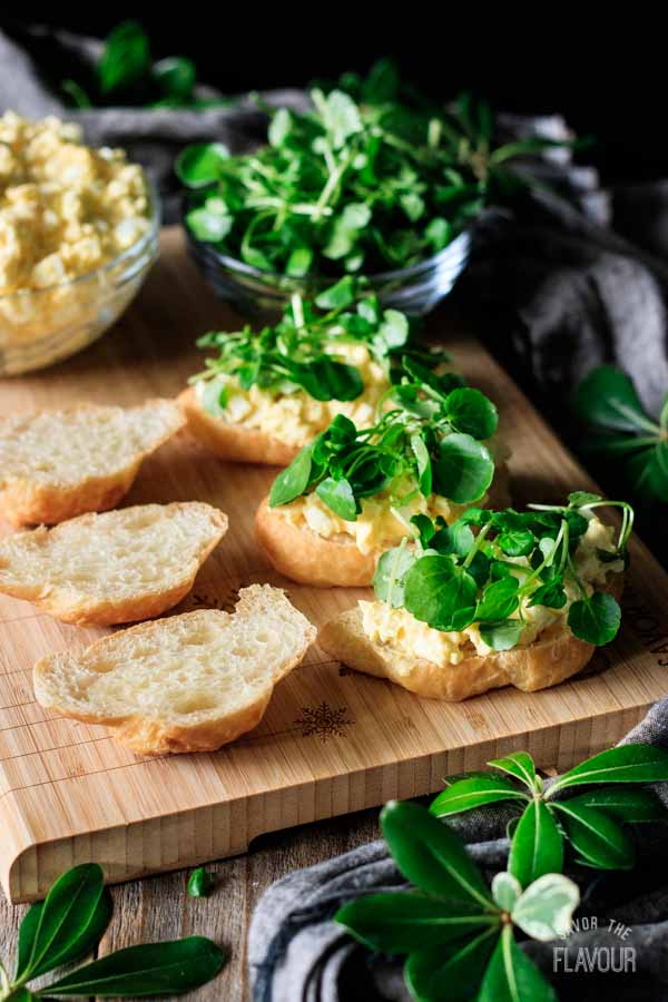 sprinkling watercress on egg salad sandwiches