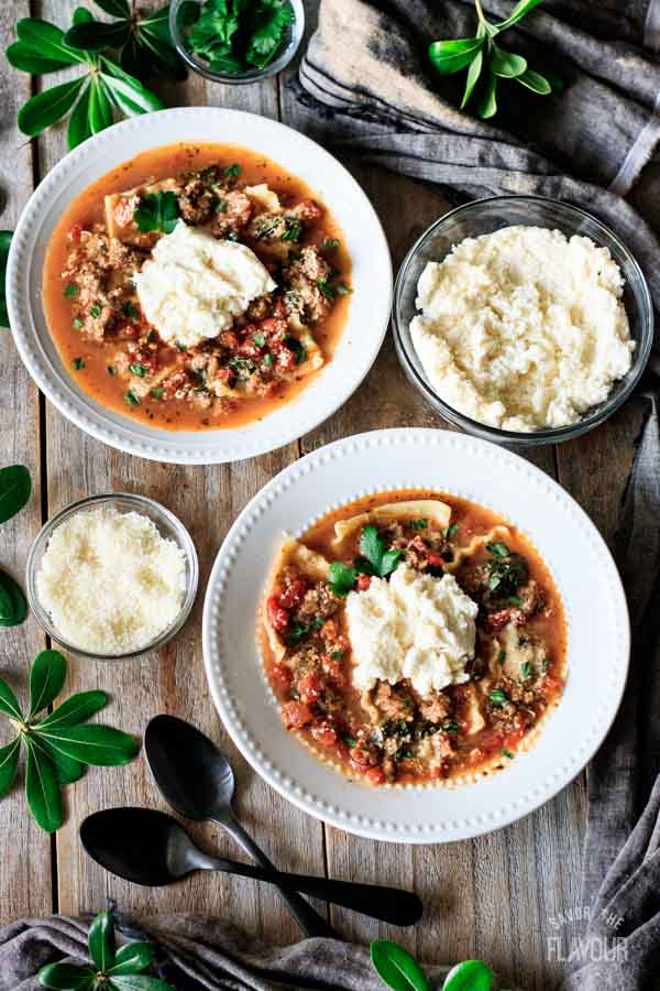 two bowls of lasagna soup with bowls of garnishes