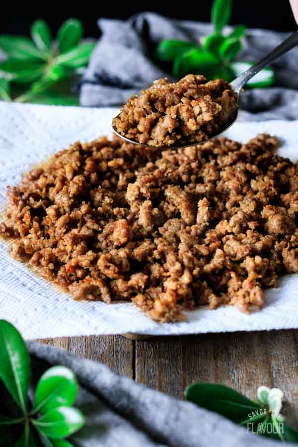 spooning cooked sausage crumbles onto a plate