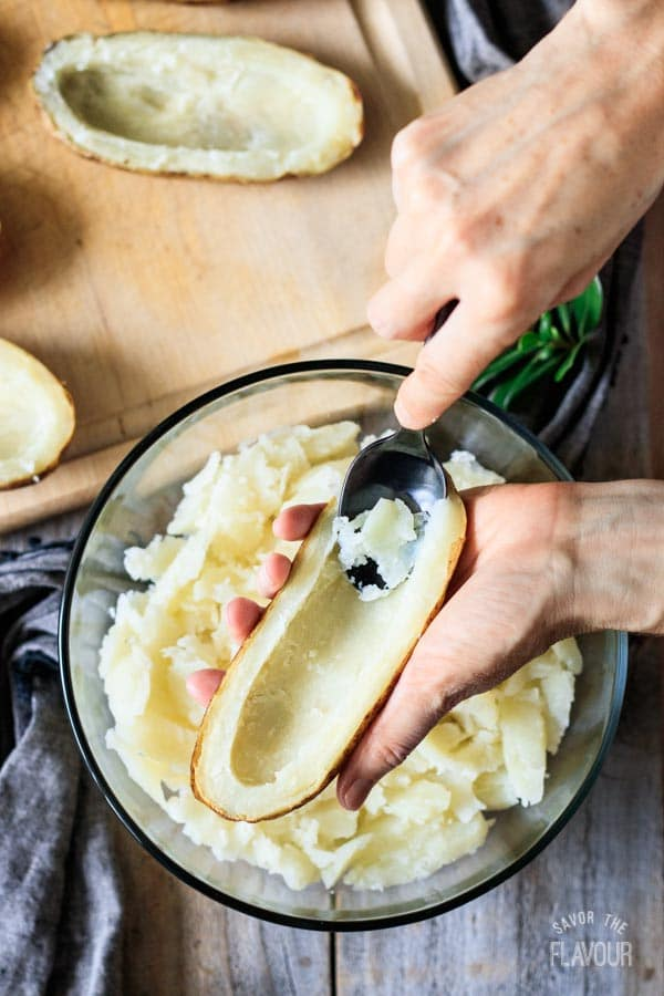 scooping out the flesh from baked potatoes