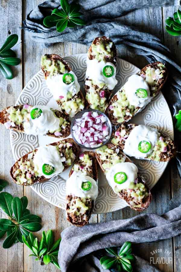 plate of loaded potato skins with red onions