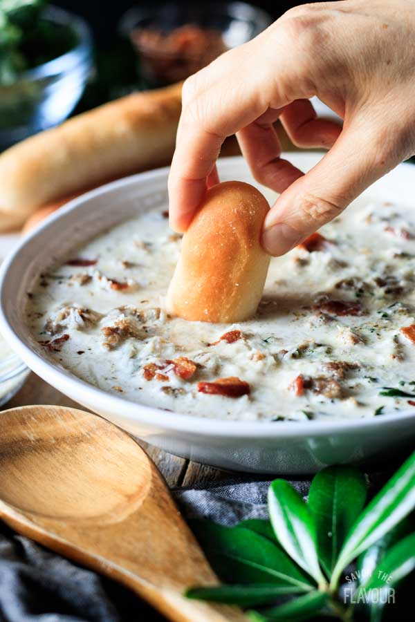 person dipping a breadstick into zuppa toscana