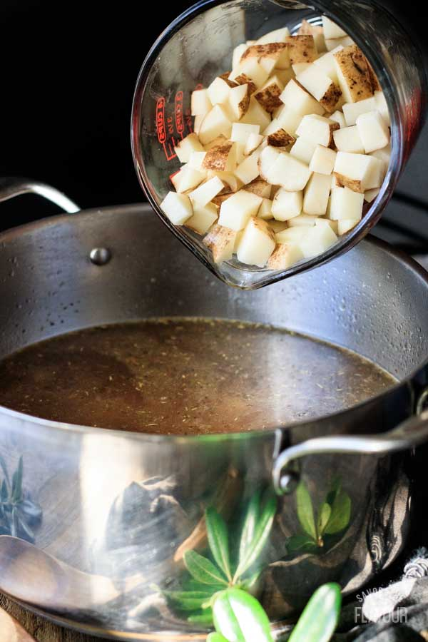 dumping cubed potatoes into a pot of soup