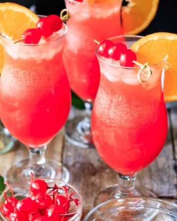 three hurricane mocktails with maraschino cherries