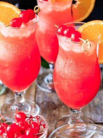 three hurricane mocktails with maraschino cherries