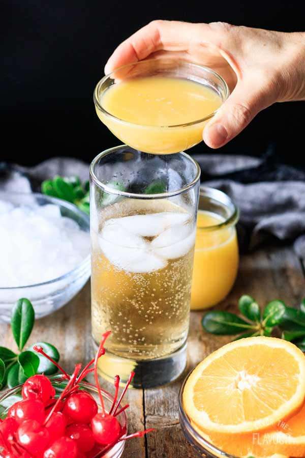 person pouring orange juice into a glass of ginger ale