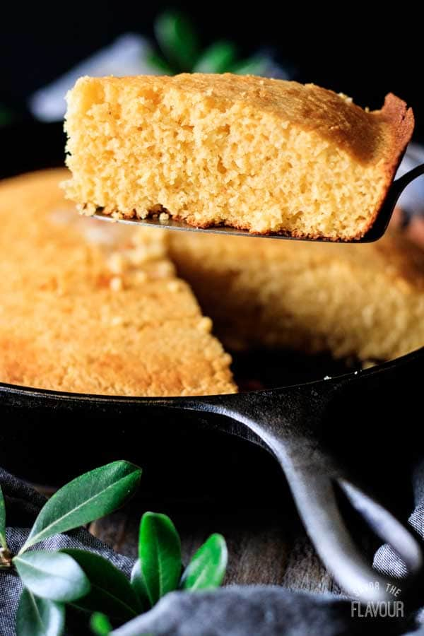 person holding a wedge of cornbread