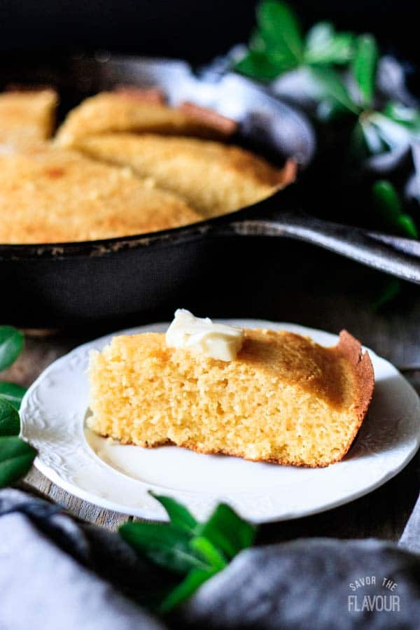 buttered wedge of cornbread on a plate