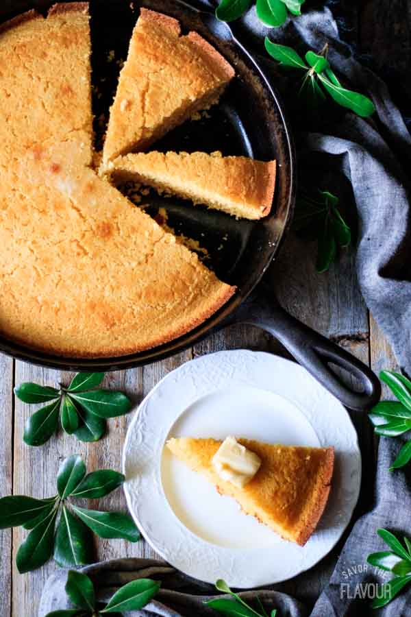 wedge of cornbread on a plate beside the skillet