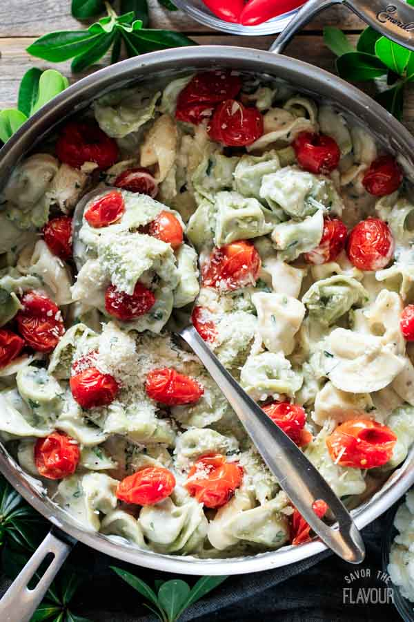 pan of basil alfredo sauce with a spoon