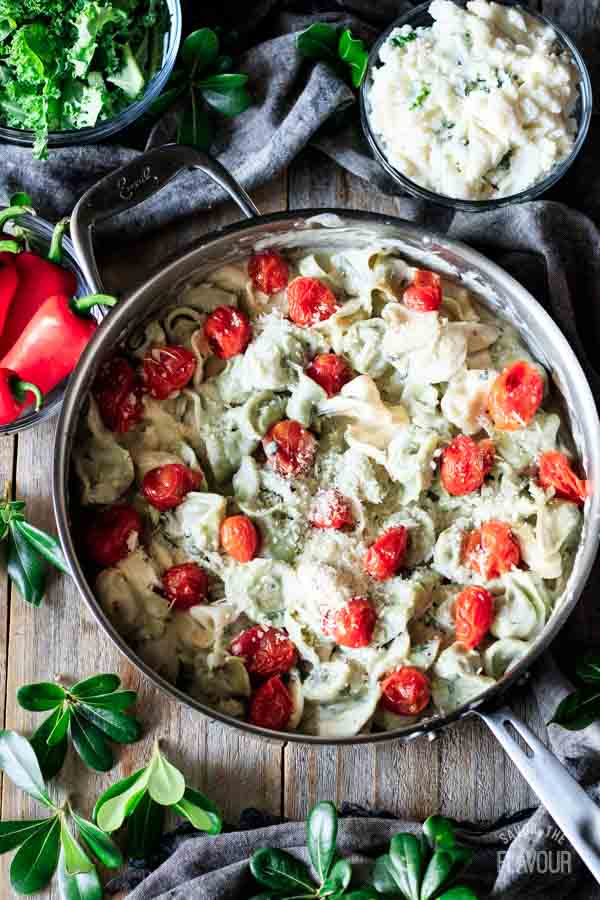 pan of tortellini mixed with alfredo basil sauce
