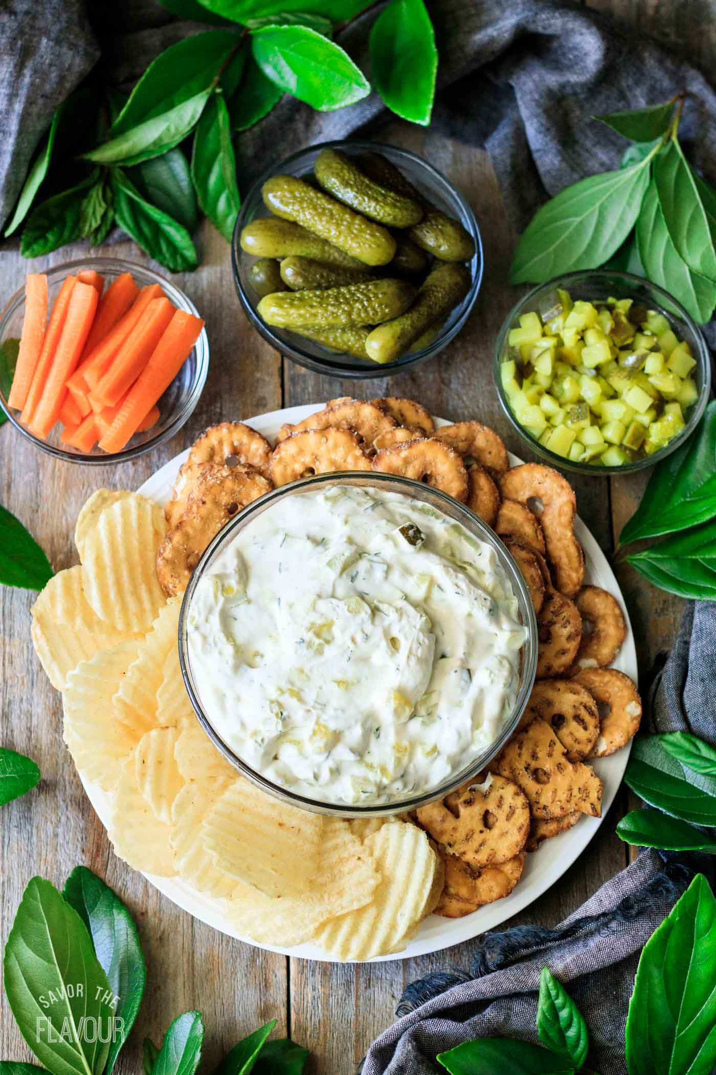 bowl of dill pickle dip with carrots, pickles, chips, and pretzels