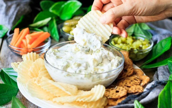 person dipping a chip into dill pickle dip