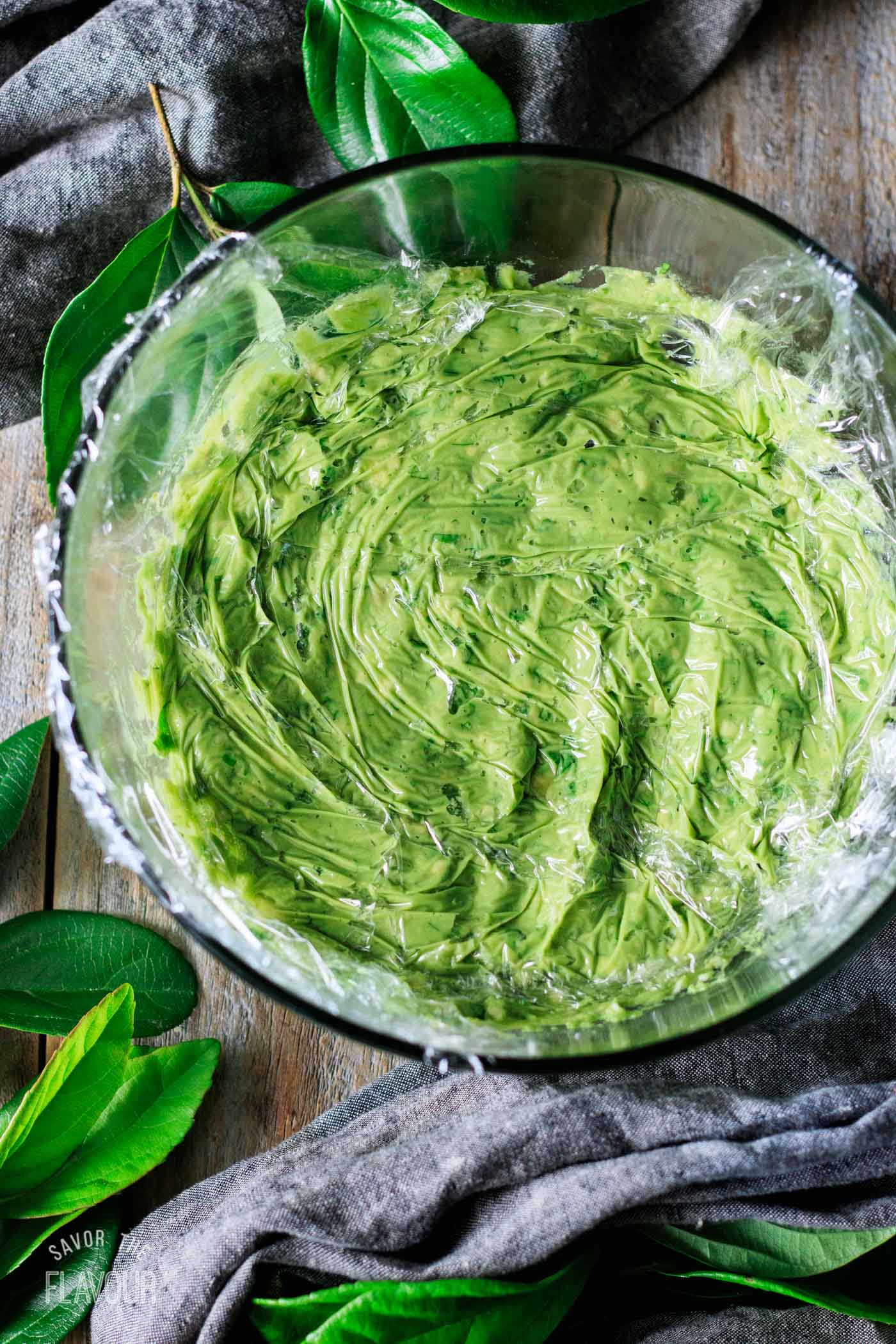 pressing plastic wrap onto surface of guacamole