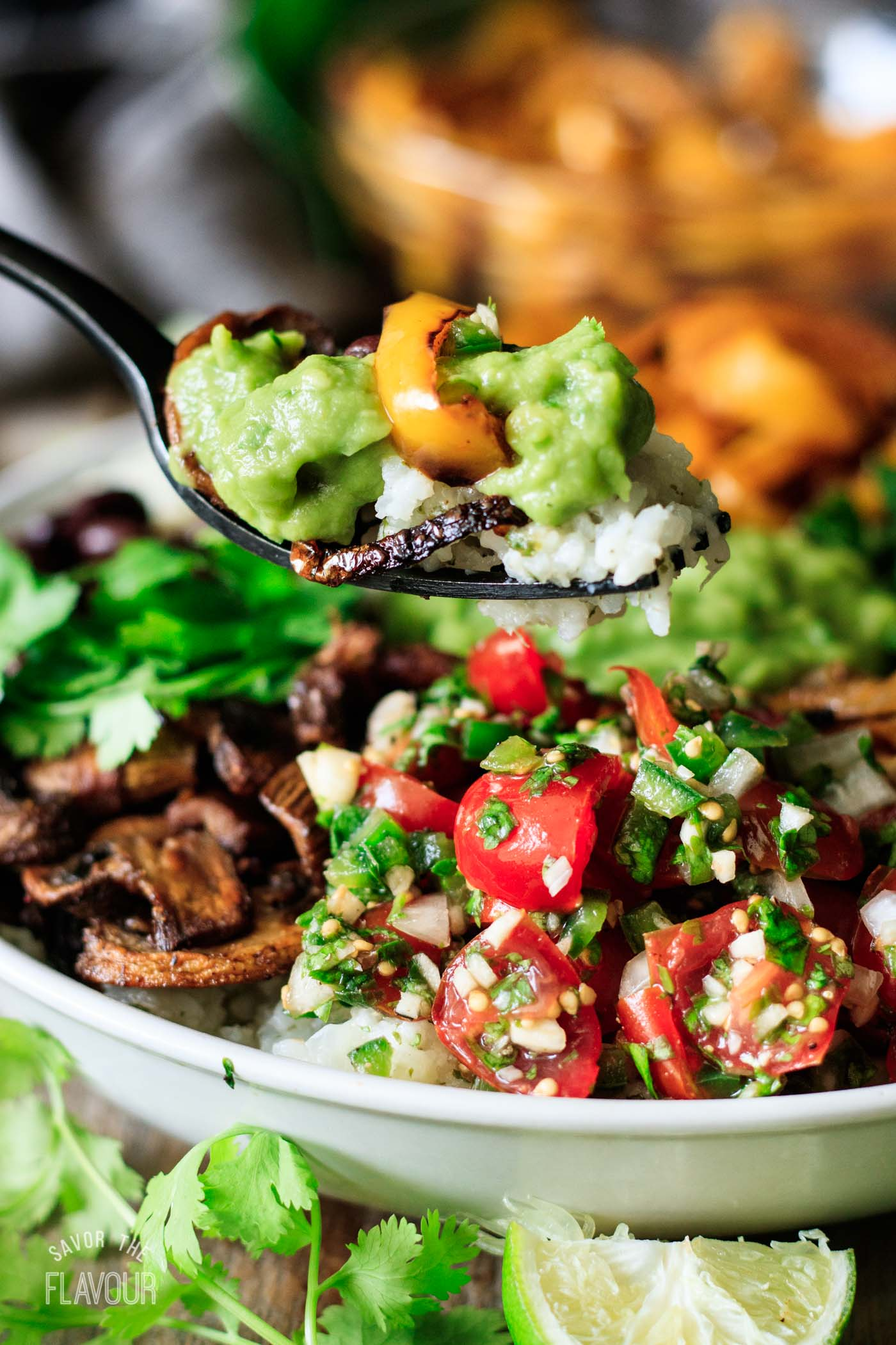 person holding a forkful of vegan burrito bowl