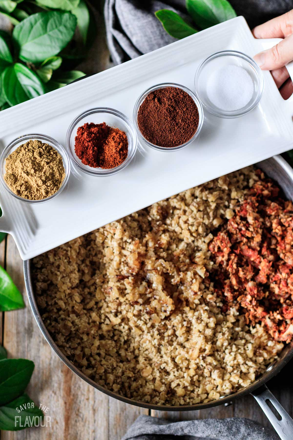 adding spices to the pan of walnut taco meat