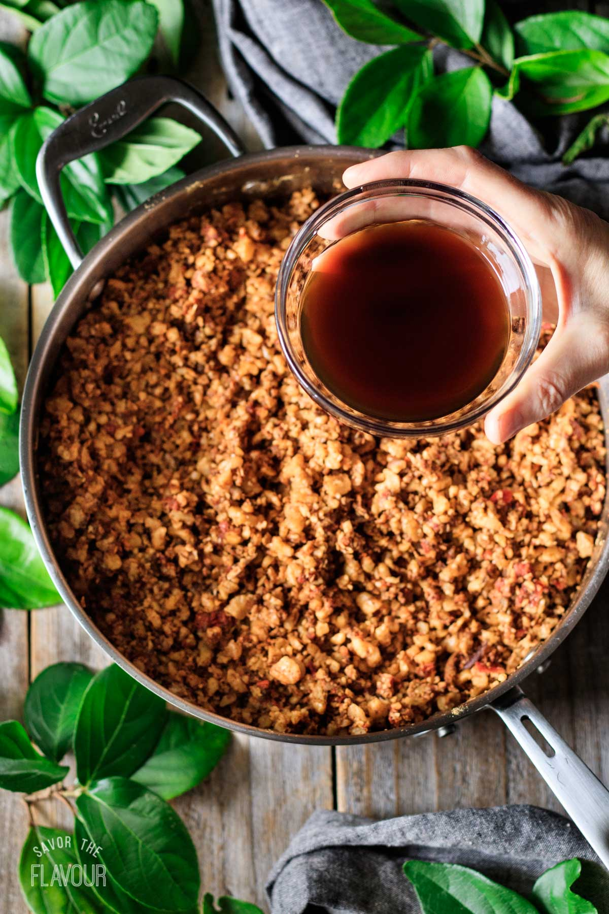 adding coconut aminos to pan of walnut taco meat