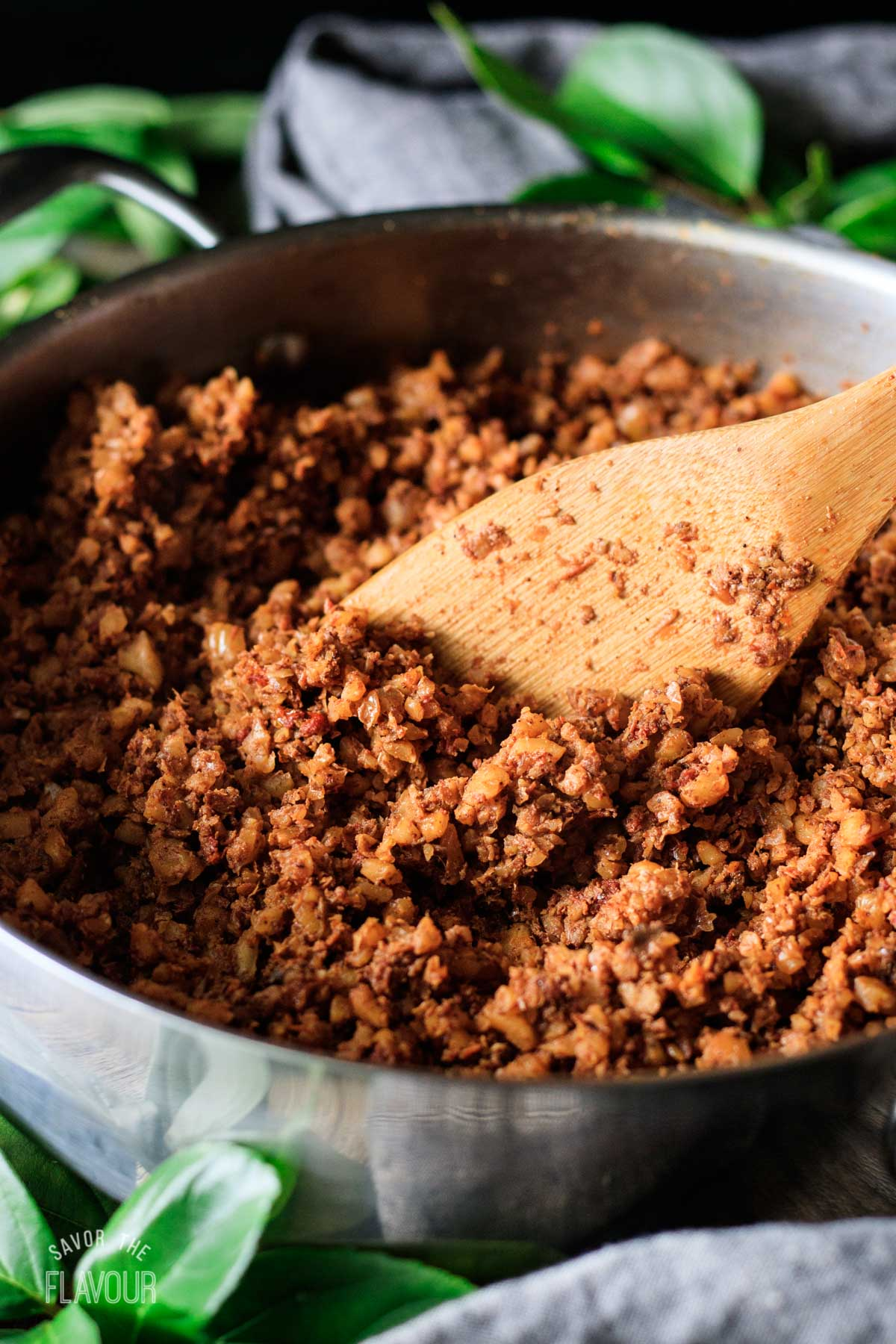person stirring walnut taco meat with a wooden spoon